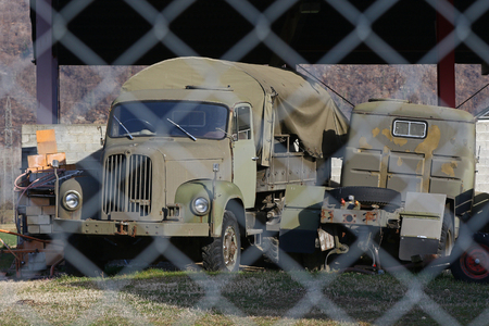 chain link fence: Old military transport truck behind a chain link fence at an army depot