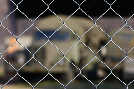 chain link fence: Old military transport truck as a background behind a chain link fence at an army depot