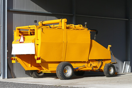 compactor: Yellow agricultural tow compactor for baling grass