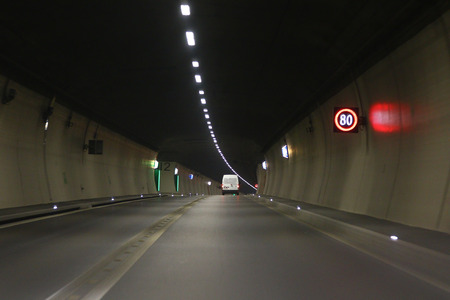 exits: Speed limit LED sign and safety exit signs in a road tunnel