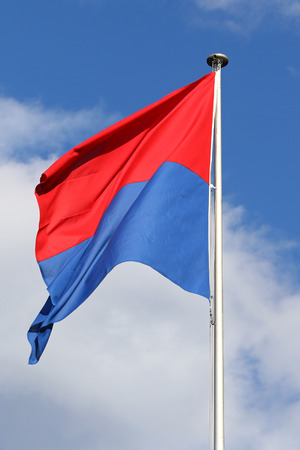 flapping: Flag of the State and Republic of Canton Ticino, Switzerland, flapping in the wind against blue skies and white clouds
