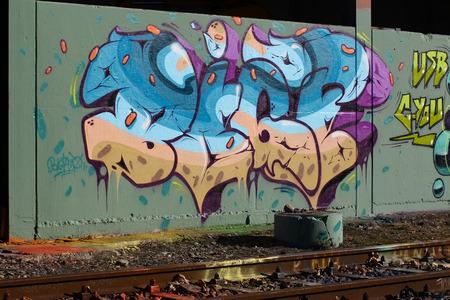 urban decline: Cadenazzo, Switzerland, February 2016, Urban wall texture along railroad tracks keep popping up along railway tracks - graffiti art abstract background