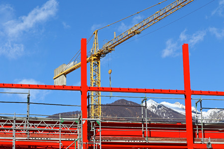 steel beam: New steel beam construction being built with yellow crane against blue skies and white clouds Stock Photo