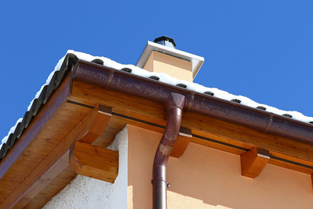 ceramic tiles: New roof top detail with ceramic tiles, chimney and copper water gutter with snow against blue skies