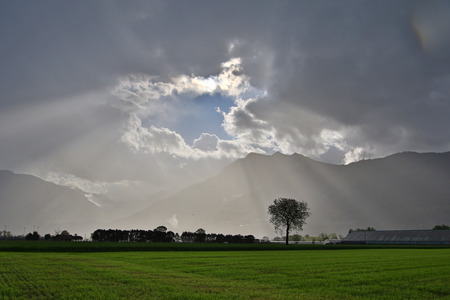 breaking through: Sun rays breaking through thunderstorm clouds over farmland Stock Photo