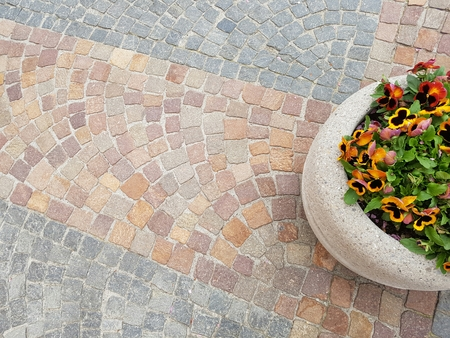 patternbackground: Pink and gray granite square cobblestone sidewalk patternbackground with flower vase and flowers Stock Photo