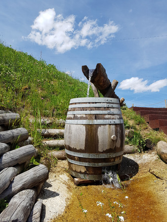 source of water: Wooden canal and barrel made into a fountain for clean, fresh source water on the side of a mountain hiking trail with blue sky