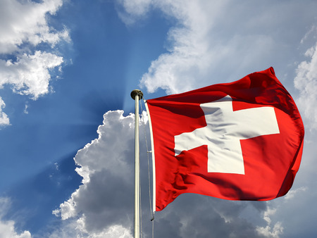Switzerland national day background: Swiss flag against blue sky with white clouds and sun  rays beaming behind it
