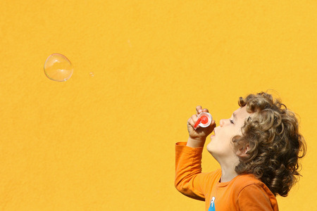 Boy blowing soap bubbles sideview against a yellow wall background