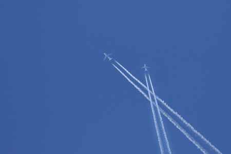 condensation: Commercial travel jets with condensation contrails crossing against blue skies Stock Photo