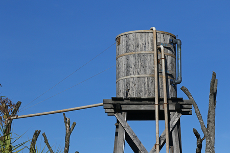 waterpipe: Old wooden water tower and pipes against blue sky