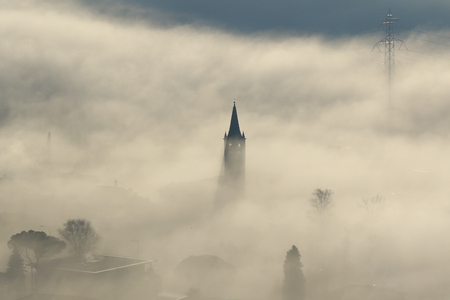 church steeple: Aerial view of power lines, pylons and church steeple peeking out of winter fog Stock Photo