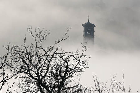church steeple: Aerial view of church steeple and trees peeking out of winter fog