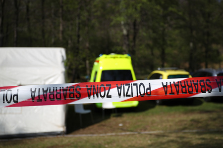 coroner: Red and white police line around a crime scene tent in a forest with ambulance,police and coroner vehicles
