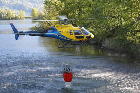 Los esfuerzos de lucha contra incendios están en marcha con helicópteros para apagar incendios forestales por encima de Gordola, Ticino, Suiza, el 19 de abril de 2017 Editorial