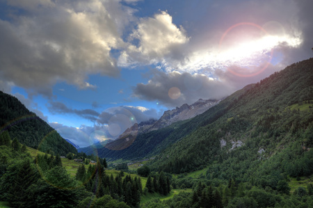 Sun peeking from behind the clouds over Val Bedretto, Switzerland Stock Photo