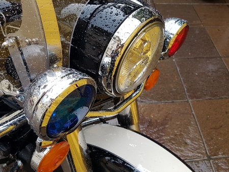 Red and blue emergency lights mounted on the front of a police motorcycle covered in water droplets
