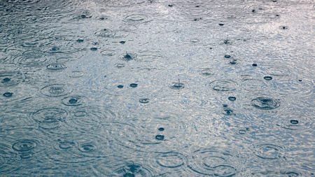 Rain drops falling in water abstract background