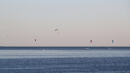 Kitesurfing off shore against a pink and blue hazy sky after sunset