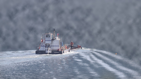 Tug boat pushing a barge on a river in low visibility, foggy conditions Stock Photo