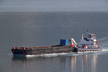 Tug boat pushing a barge on a river