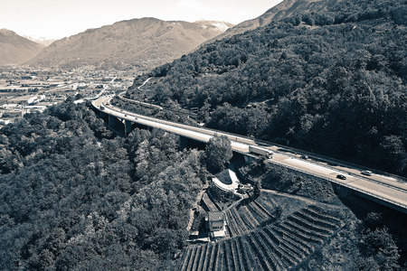Split tone aerial view of the A2 freeway going up Monte Ceneri Pass in Ticino, Switzerland