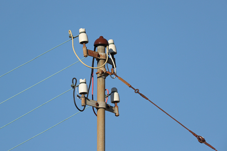 Powerlines at an electric metal pole against blue skies
