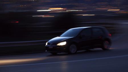 Black car racing at night motion blur