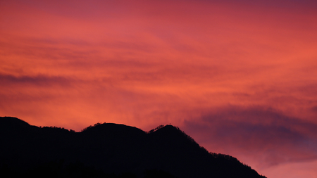 Colorful sunset sky with silhouette of mountain with cross