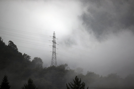 High voltage powerlines and pylon in fog and clouds