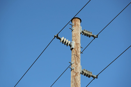 Powerlines at an electric wooden pole against blue skies