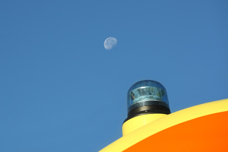 Detail of roof and blue emergency light against a blue sky with moon