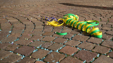 Cobblestone pavement with carnival confetti and paper ribbons background Stock Photo