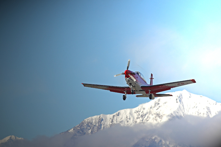 Single engine airplane landing at a high altitude mountain airport in the Alps in front of snow covered peaks