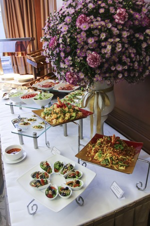 catered: Assorted fresh salads displayed on a buffet in individual containers at a catered event or celebration, receding perspective Stock Photo