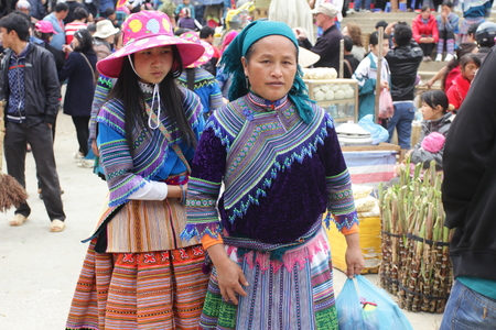 traditional goods: SAPA, VIETNAM - FEBRUARY 08, 2015: Hmong women at Bac Ha market in Northern Vietnam. Bac Ha is hilltribe market where people come to trade for goods in traditional costumes.
