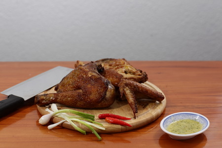 roasted chicken on gray plate, on wood table. Stock Photo