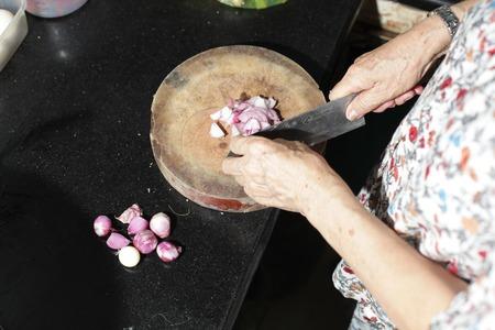 scallions: Old Woman cutting fresh scallions. Stock Photo