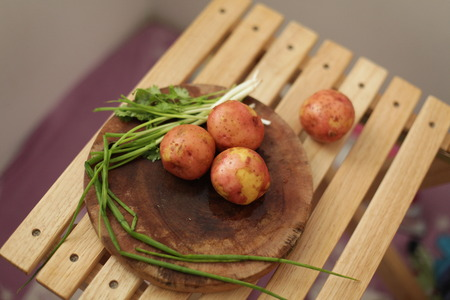 Sliced, peeled raw potatoes with a knife on a board, and scallions Stock Photo
