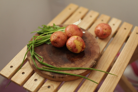 scallions: Sliced, peeled raw potatoes with a knife on a board, and scallions Stock Photo