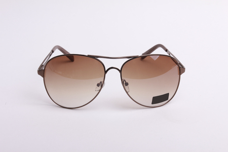 Brown-rim eyeglasses in white background.
