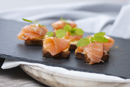 Smoked salmon toast with mint leaf on black stone and old wooden board with space for your text