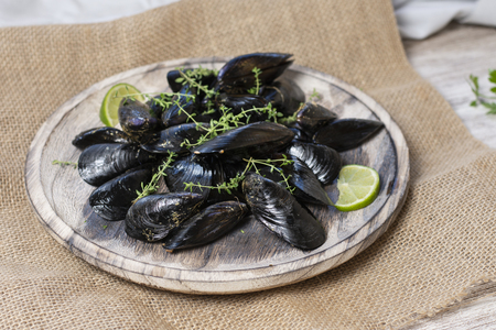 freshly caught rock mussels on old wooden plate