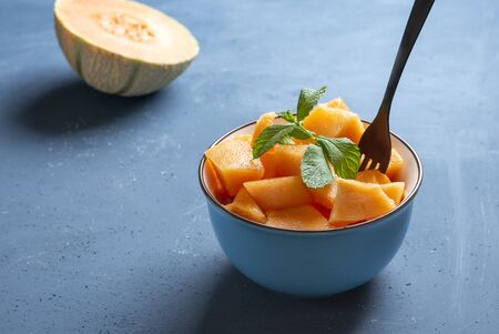 Fresh melon cut into pieces in a bowl and background blue