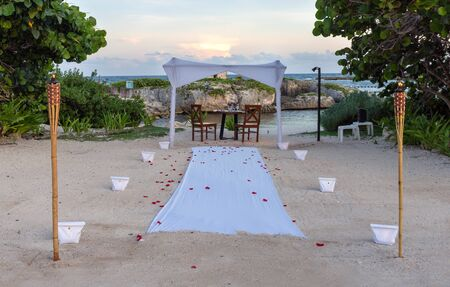 2185000all prepared for a romantic dinner with candles, torches and rose petals on the sea sand beach against the sunset: wedding day, marriage proposal, Valentines day or honeymoon concept