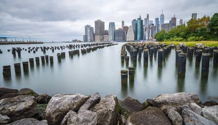 Manhattan financial district on a beautiful summer morning. Long exposure photo of the financial district of Manhattan on a cloudy summer morning, on the old pier