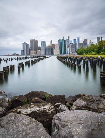 Manhattan skyline with an old pier in the foreground. View of downtown Manhattan at sunset from Brooklyn Bridge Park