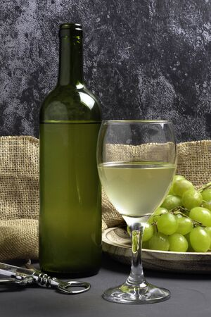White wine glass with grapes in cellar atmosphere