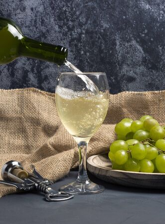 filling glass of white wine with grapes in cellar atmosphere