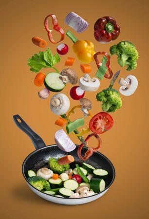 grilled fresh vegetables flying isolated on orange background